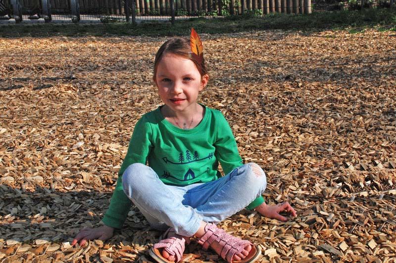 Kind sitzend, in Langarmshirt, grün, mit Indianercamp-/Pfeilmotiv in dunkelblau