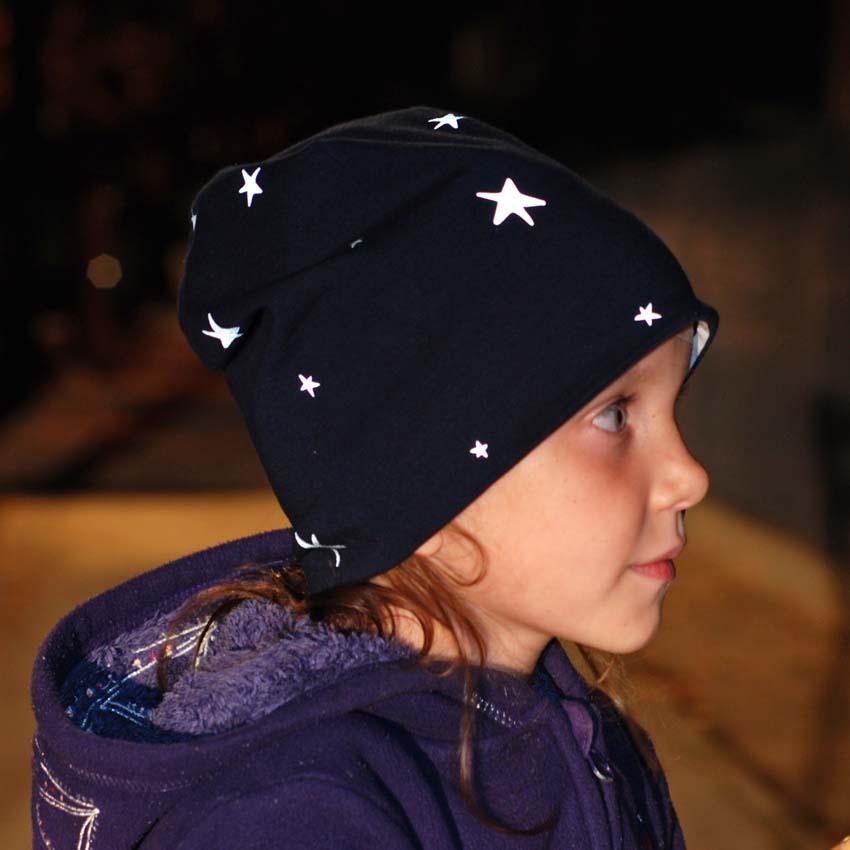 Mädchen im Dunkeln mit Mütze in dunkelblau mit reflektierenden Sternen