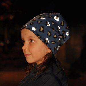 Mädchen im Dunkeln mit blauer Mütze mit reflektierendem Leoprint
