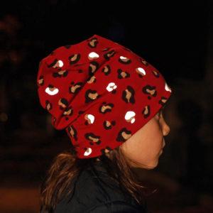 Rückansicht von Mädchen im Dunkeln mit roter Mütze mit reflektierendem Leoprint
