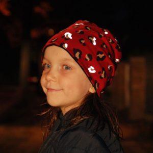 Mädchen im Dunkeln mit roter Mütze mit reflektierendem Leoprint
