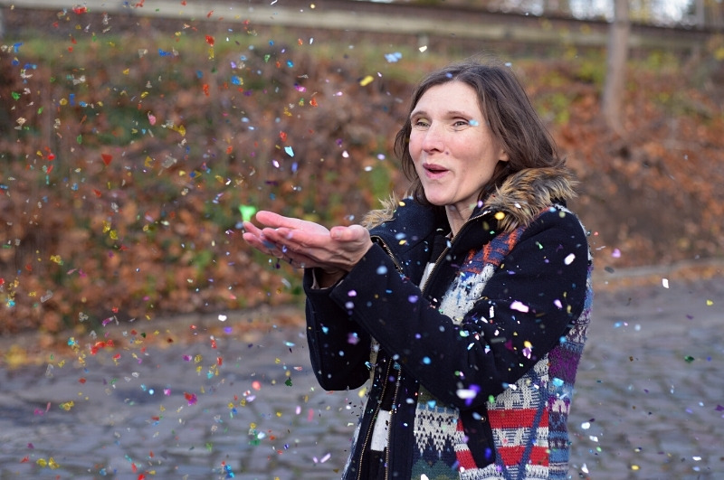 Blogbeitragsbild Happy Birthday - Frau pustet Geburtstagskonfetti