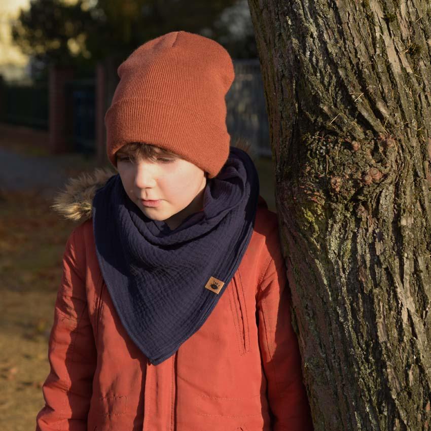 Junge neben Baum mit dunkelblauem Musselin Halstuch über rostroter Jacke