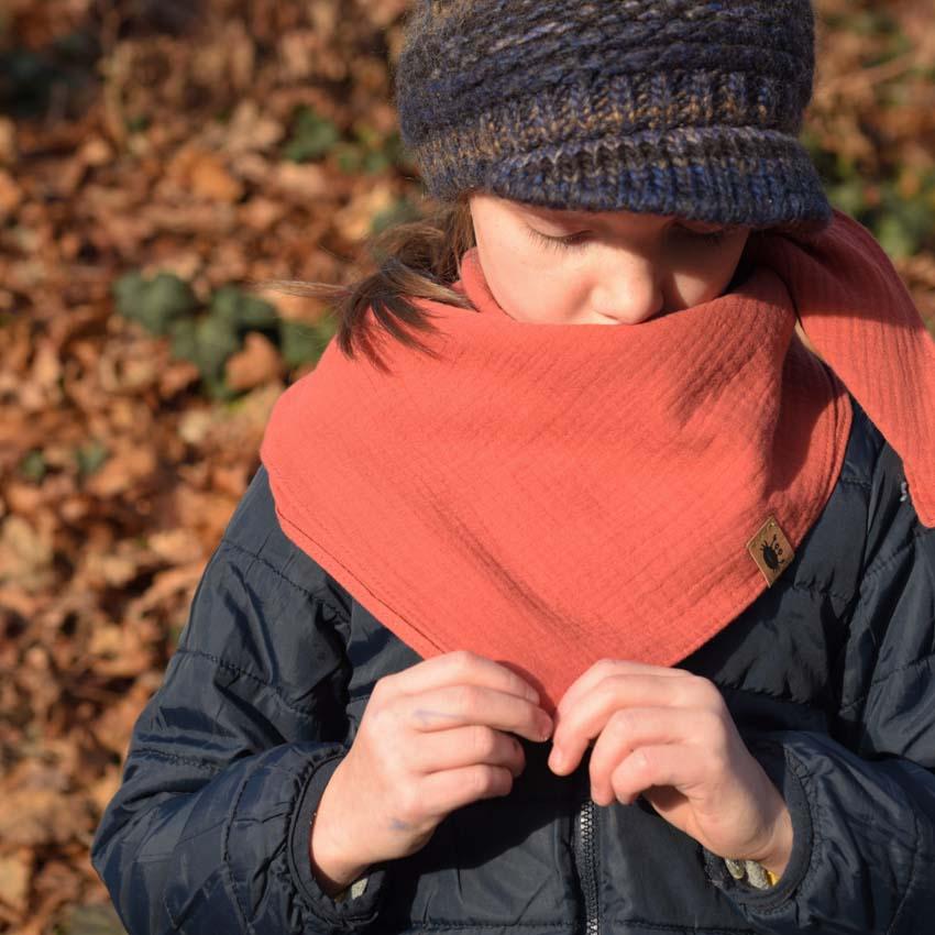 Mädchen draußen mit Musselin Halstuch in rusty-rose über dunkelblauer Jacke