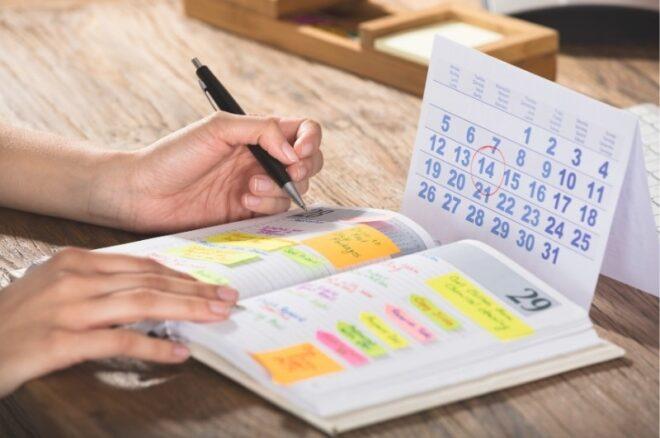 Close-up von Person, die Termine in Kalender erfasst.