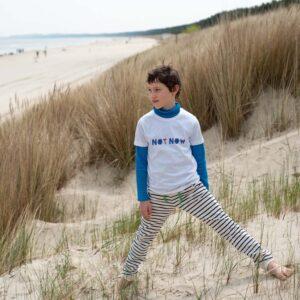 Junge am Strand in Dünen stehend in marine-natur gestreifter Hose