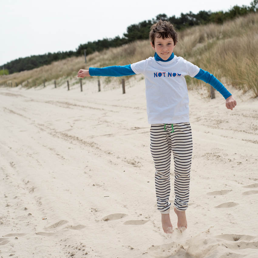Junge am Strand in die Luft springend in marine-natur gestreifter Hose