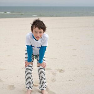 Junge am Strand in marine-natur gestreifter Hose Meer im Hintergrund