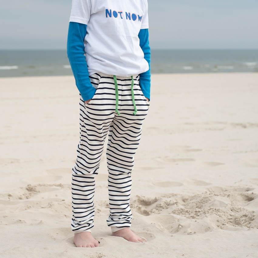 Detailbild von Kind am Strand in marine-natur gestreifter Hose mit grünem Dekoband am Bund